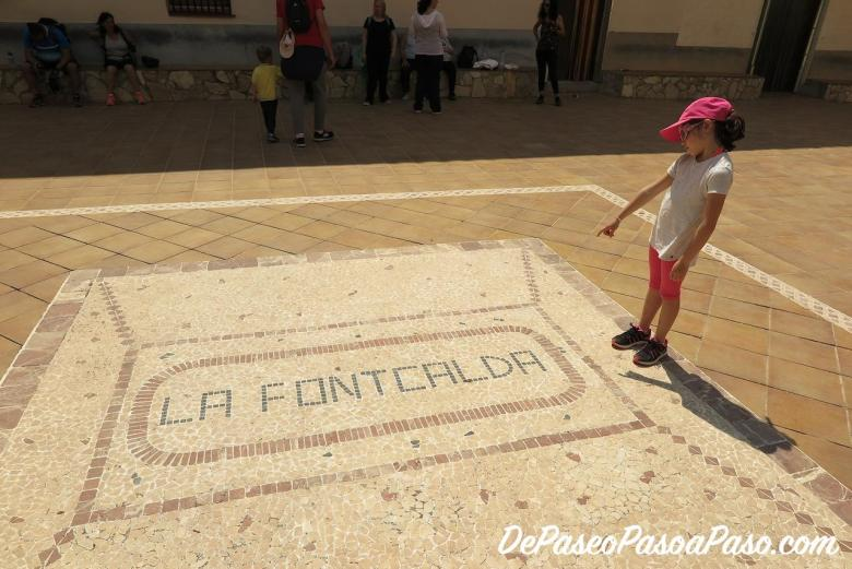 Niña señalando cartel de La Fontcalda en el suelo