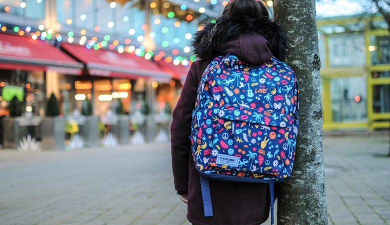 niña con mochila de espalda en parque temático