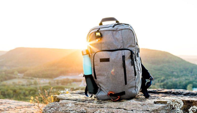 mochila con botella de agua sobre una roca y sol detrás