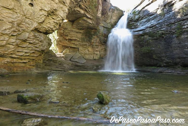 Vista al salto de agua y agujero en la pared de roca
