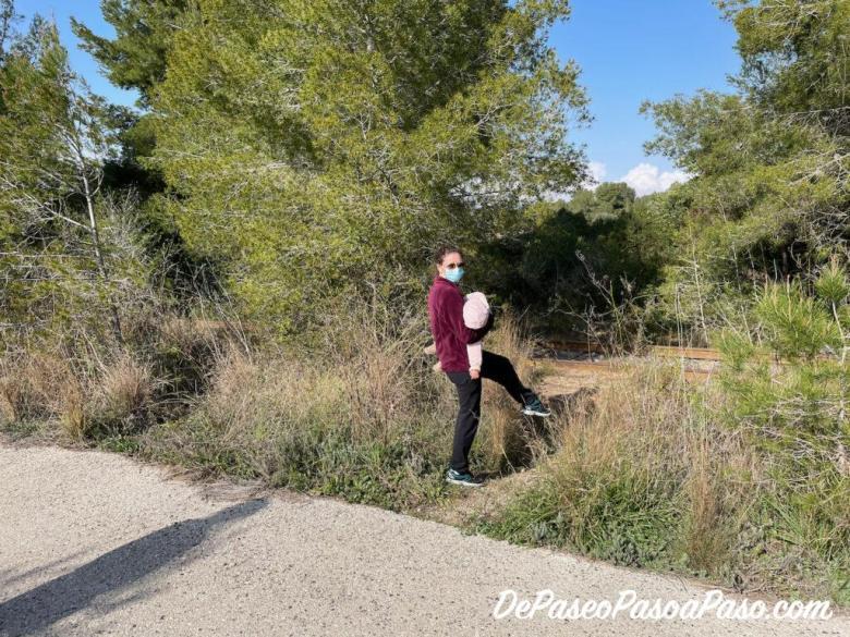 mujer buscando el paso sin vegetación para llegar a la vía de tren abandonada