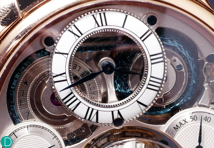 The dial with the hour subdial, and below, the blue chain wrapped around the fusee system. The fusee and chain provides an elegant way to provide the escapement with constant force.