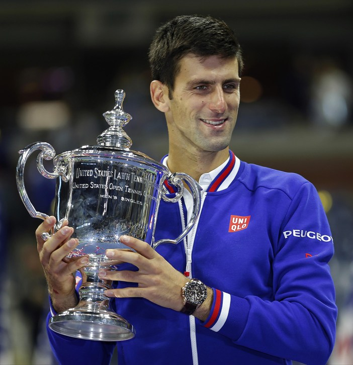 Novak Djokovic, of Serbia, holds up the championship trophy after defeating Roger Federer, of Switzerland, in the men's championship match of the U.S. Open tennis tournament, Sunday, Sept. 13, 2015, in New York. (AP Photo/Julio Cortez)