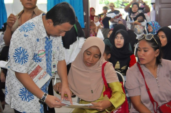 Kepala BPJS Kesehatan Cabang Kota Depok Nurifansyah sedang menjelaskan cara mengisi formulir pendaftaran menjadi peserta JKN-KIS.