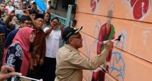 Walikota Depok Mohammad Idris sedang melukis di kampung warna warni Pondok Cina, Selasa (19/12/2017).