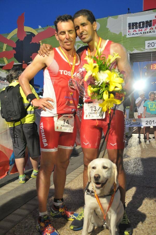 Con sólo siete meses de entrenamiento, Enhamed consiguió terminar el Ironman de Lanzarote en poco más de 13 horas. En la foto junto a su entrenador Andreu Afonso y su perra-guía Gayla.