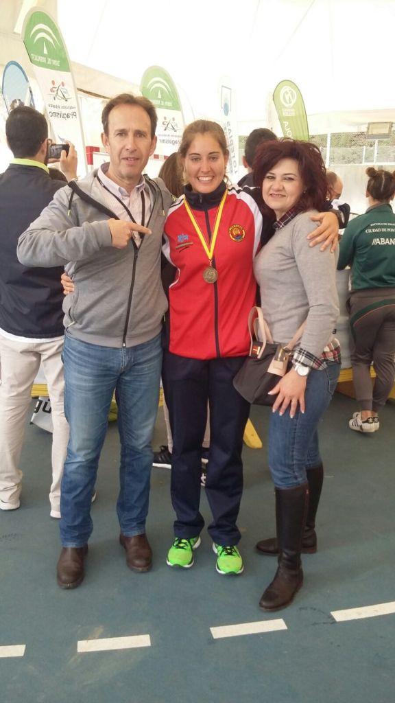 Estefanía Fernández junto a sus padres mostrando la medalla de ORO
