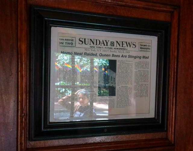 In this Friday, June 14, 2019, photo, a framed newspaper clipping, right, hangs near the entrance of the Stonewall Inn in New York, headlining the 1969 riots that followed a police raid of the bar.   Some of the coverage of rioting was itself a…