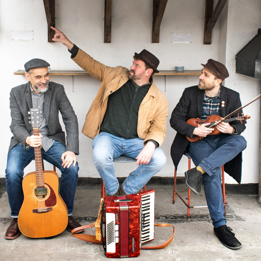 The three members of the Black Smock Band sit on a wooden bench with their instruments; a guitar, an accordian and a violin