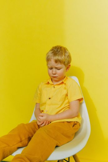 boy-in-yellow-button-up-shirt-sitting-on-white-chair-near-3771681