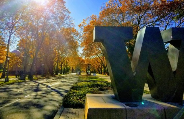 """The """"W"""" statue at the entrance to the UW campus, with fall-colored trees and the Jacobsen observatory in the background."""