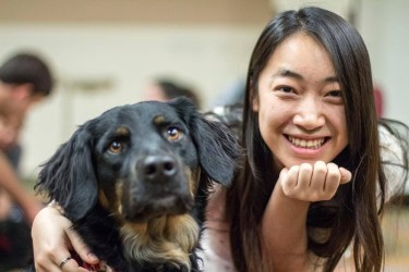 Photo of a girl with long black hair, she is hugging a black dog and both of them looking at the camera