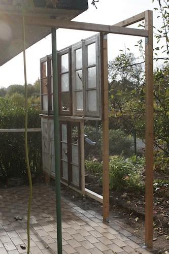 die ersten Gewächshausfenster werden an die Balken geschraubt