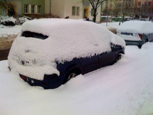 Eingeschneites Auto am Straßenrand