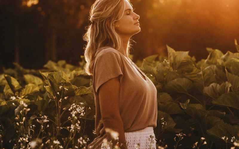 dreamy woman standing on lush field at sunset