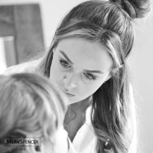 A make up artist carefully applies make up to a Bride