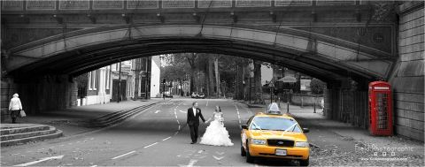 A Bride and Groom walk under a classic Bridge with a Yellow New York Cab next to them. The picture is black and white except for the Yellow Cab and a Red traditional phone box.