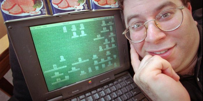"""FILE - Sanford Wallace, president of Cyber Promotions, poses with his computer and cans of Spam processed meat in Dresher, Pa, in this May 8, 1997 file photo. Wallace, the self-proclaimed """"Spam King,"""" pleaded not guilty during an initial court appearance Thursday Aug. 4, 2011 after being indicted July 6 on six counts of electronic mail fraud, three counts of intentional damage to a protected computer and two counts of criminal contempt. The indictment filed in San Jose federal court said Wallace compromised about 500,000 Facebook accounts between November 2008 and March 2009 by sending massive amounts of spam through the company's servers on three separate occasions. (AP Photo/Dan Loh)"""