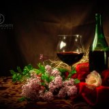 Glass and Bottle of Red Wine in Elegant Setting