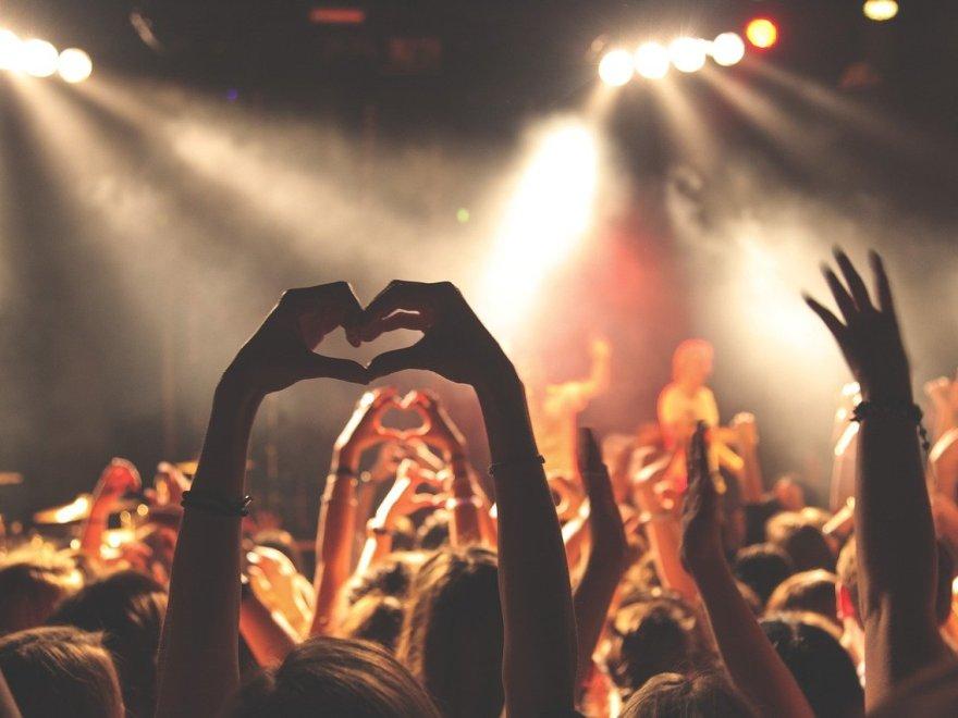 Menschen halten ihre Hände bei einem Konzert hoch und formen mit den Fingern ein Herz.