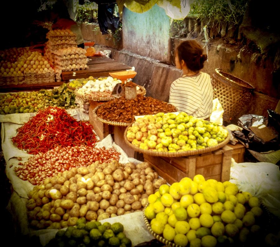 Frau mit dem Rücken zur Kamera. Marktstand mit Obst, Gemüse und Gewürzen.