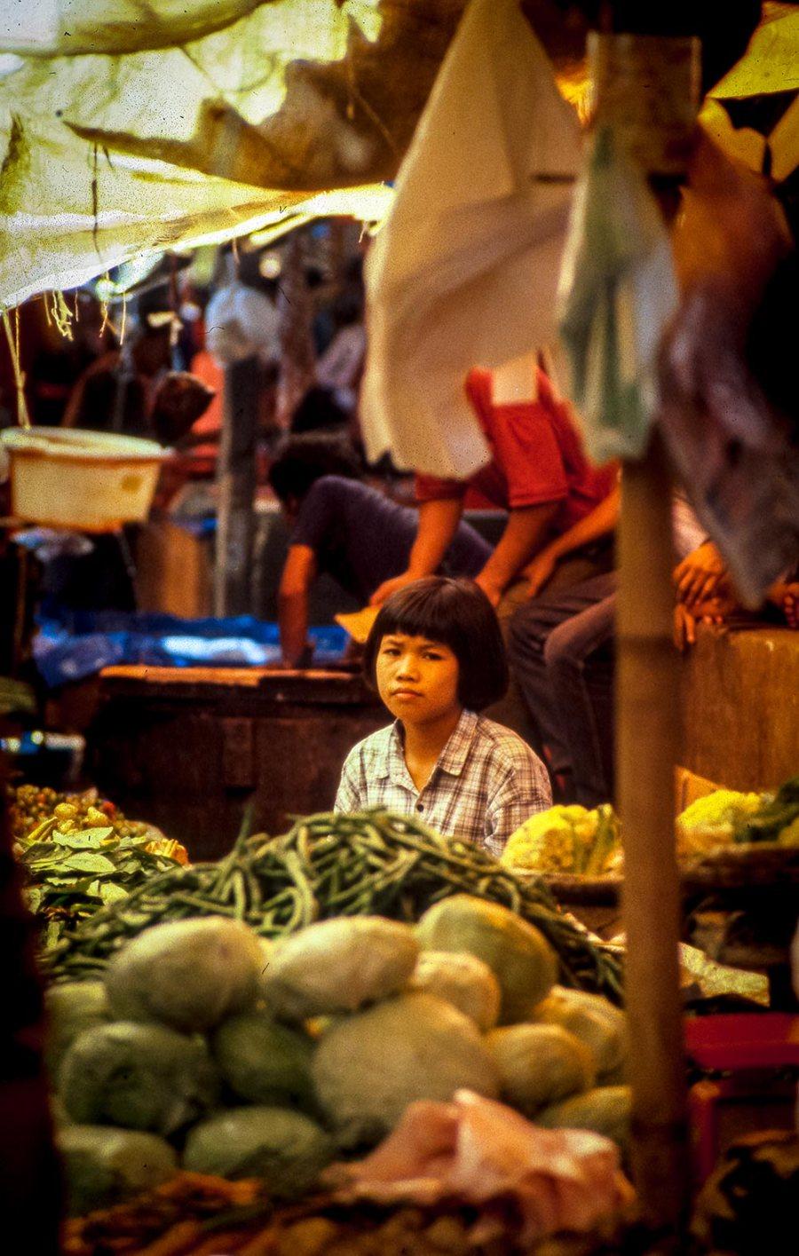 Mädchen an einem Stand mit Gemüse