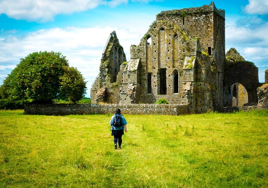 Irland: Rock of Cashel: Frau mit Rucksack wandert, grüne Wiese, grüner Baum, Ruine derhalbhartemann.com