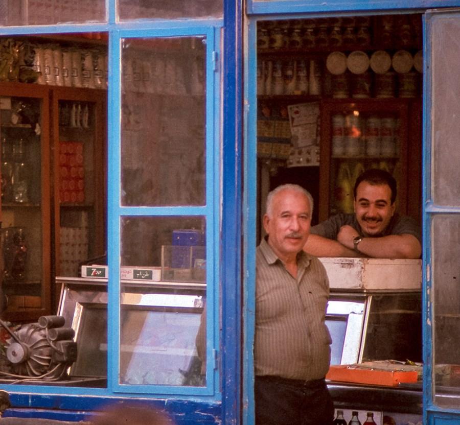 Strassenszene. 2 freundliche Herren in einem kleinen Geschäft