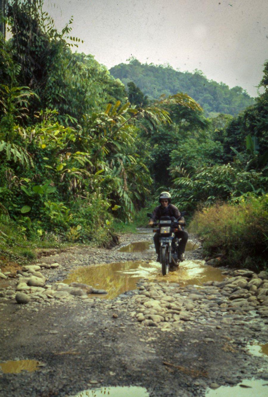 Mit dem Motorrad auf einer unwegsamen Piste im Urwald Sumatras.