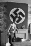 "05 Jun 1965 --- Original caption: 6/5/1965-A huge swastika adorns the wall over the fireplace as George Lincoln Rockwell leans on the mantlepiece. Rockwell feels that his main political strength in America lies ""with the working man."" He is confident of victory in his campaign to be Governor of Virginia. --- Image by © Bettmann/CORBIS"