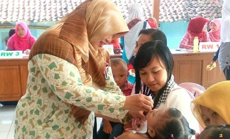 Bidan Desa Dermaji, Neneng Supriati sedang meneteskan vaksin polio ke salah satu balita