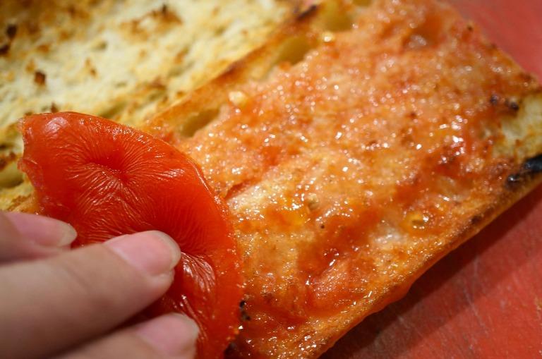erst Knoblauch, dann Tomate auf dem Brot verreiben