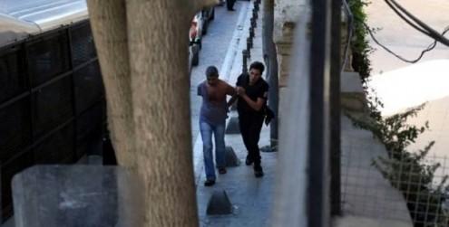 Dogan Guzel, de camisa rasgada, sendo conduzido à carrinha da polícia após o encerramento do jornal Ozgur Gundem. Foto: Firat News