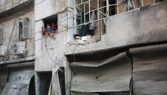 Na imagem, crianças sírias aparecem nas janelas de um edifício destruído pelos bombardeios em Alepo. Foto: AFP.