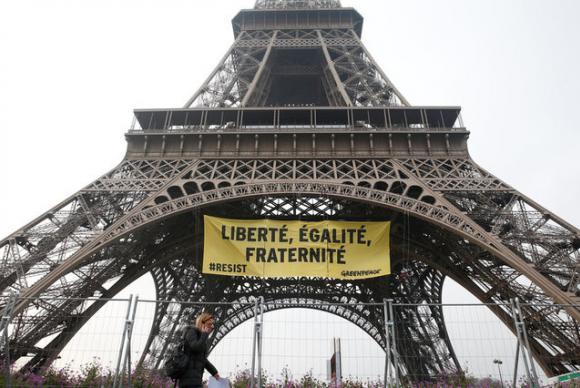 """Uma mulher passa pela Torre Eiffel enquanto ativistas do Greenpeace abrem um faixa gigante com """"Liberdade, Igualdade, Fraternidade"""" no monumento, em Paris (Foto: Reuters/Gonzalo Fuentes)"""