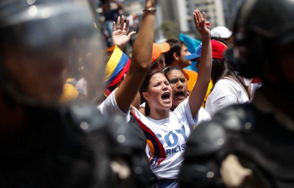 CAR119. CARACAS (VENEZUELA), 21/03/2013.- Seguidores chavistas y opositores marchan hoy, jueves 21 de marzo de 2013, en el centro de Caracas (Venezuela). Cuatro estudiantes opositores resultaron heridos tras ser agredidos presuntamente por jóvenes chavistas cuando trataban de llegar al Consejo Nacional Electoral (CNE) para exigir elecciones justas en Venezuela, según fuentes de la marcha opositora. EFE/David Fernández