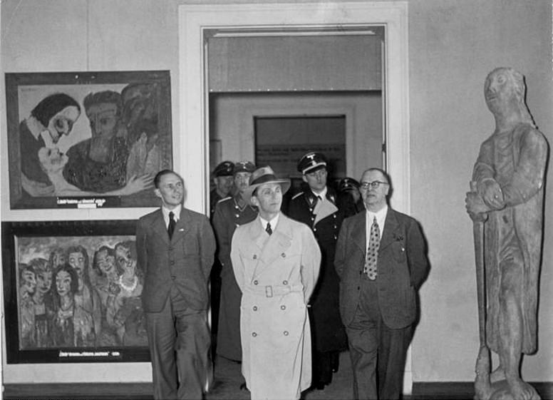 Exposición «arte degenerado» en Múnich (1937). El nazi Joseph Goebbels (con gabardina) y a la izquierda dos obras de Nolde: Cristo y la pecadora y Las vírgenes sabias y las vírgenes necias. Wikimedia
