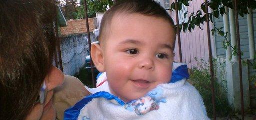 imagem do Kauê quando bebezinho de colo ainda, sorrindo envergonhado.