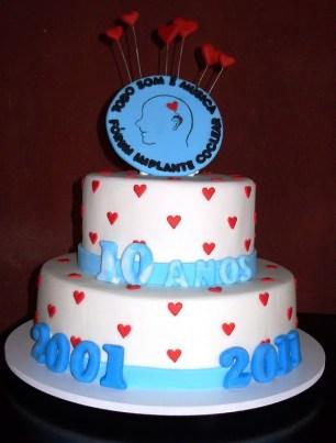 Imagem de bolo de dois andares, com o logo do FIC (um perfil de rosto com um aparelho em forma de coração no lugar da parte externa do implante). O bolo está decorado com corações e a frase 10 anos - 2001 - 2011