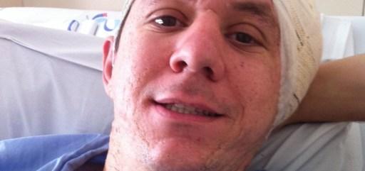imagem do Marcelo deitado no leito hospitalar, vestindo avental e com um curativo em forma de turbante, que protege a orelha onde foi inserido o implante coclear