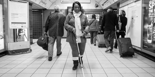 Imagem de uma mulher negra segurando a bengala-guia andando numa estação de metrô de Londres com várias pessoas ao redor.
