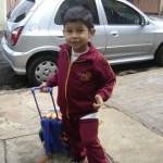 Kadu com uniforme escolar carmesim, segurando a mala de rodinhas onde provavelmente carrega o material, com cerca de 5 anos de idade.
