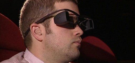 Imagem do óculos que reproduz legendas. Lembra um pequeno binóculos preto, com hastes que o prendem às orelhas.