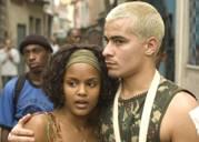 Imagem de cena do filme. Dois atores abraçados em primeiro plano, um loiro oxigenado e uma negra. Ambos olham para algo, com olhar desconfiado. Em segundo plano, dois outros homens. Pode-se ver ao fundo, ainda que meio fora de foco, construções típicas de favelas.