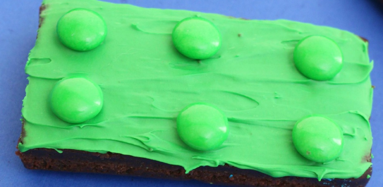 brownie decorated with green icing and candy to look like a LEGO