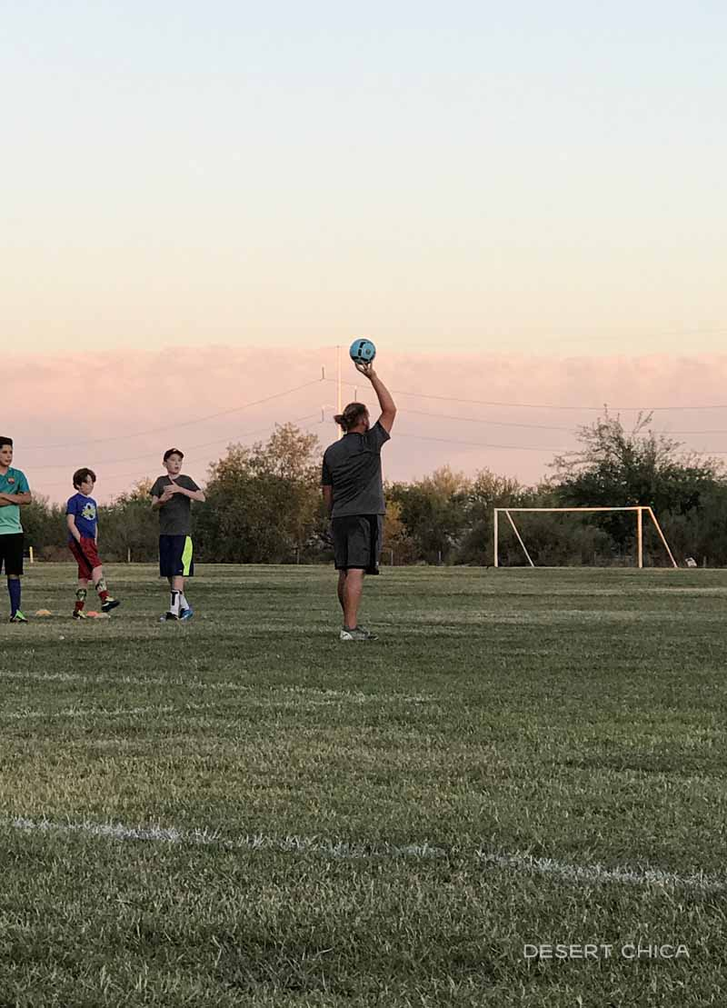 Kids with their coach on a soccer field