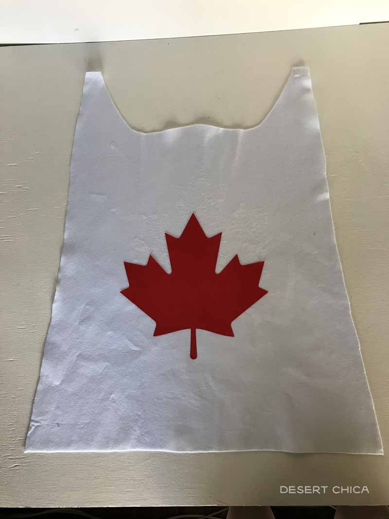 white cape with red maple leaf
