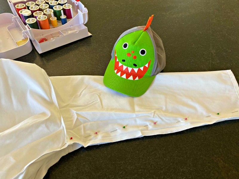 sleeve of white shirt with green dinosaur hat