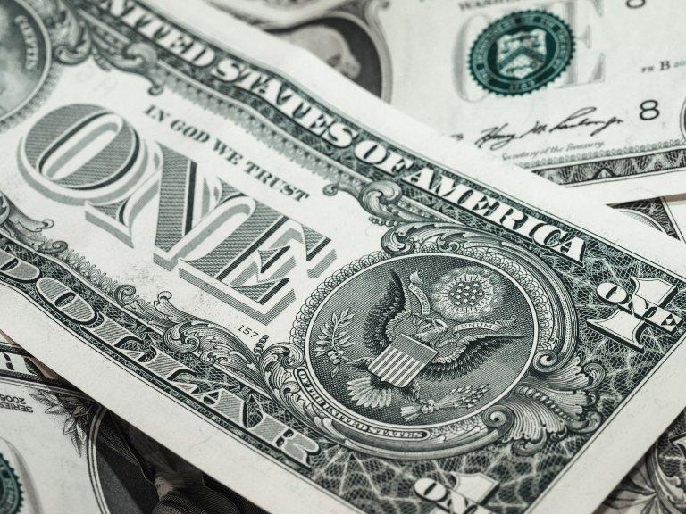 Dinero amontonado con un billete de dólar sobresaliendo.