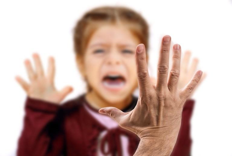 Rostro borroso de niño con cara de miedo antes de que le den una bofetada.